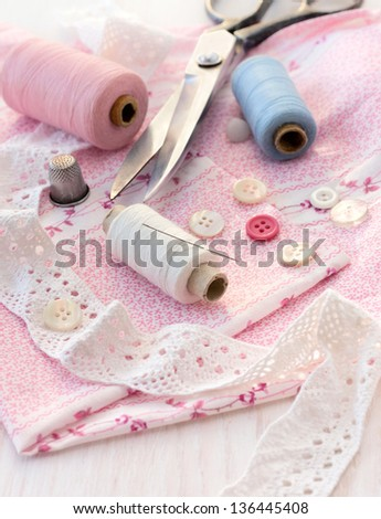 sewing accessories - thread, scissors, needles, buttons, ribbons on the fabric - stock photo
