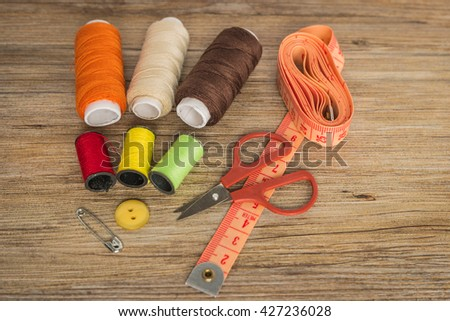 Sewing background. Accessories for needlework on wooden background. Spools of thread, scissors, buttons, measuring tape, sewing supplies. Set for needlework top view with copy space. - stock photo