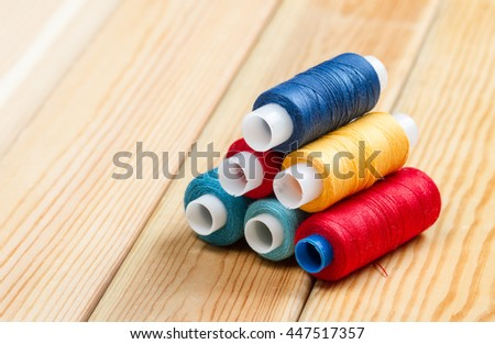 Sewing background Bobbins with colorful threads on wooden table background