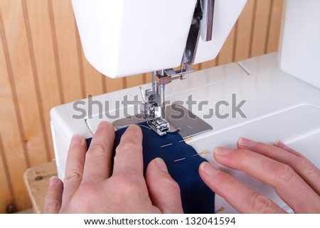 Sewing blue fabric on sewing machine - stock photo