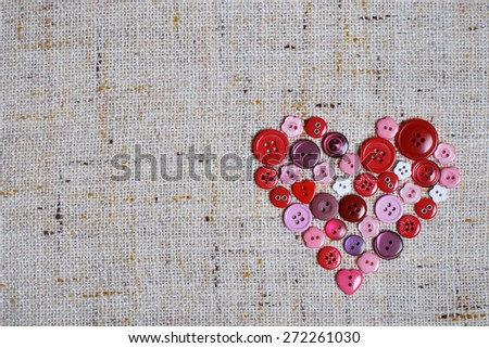Sewing buttons in a heart shape - stock photo