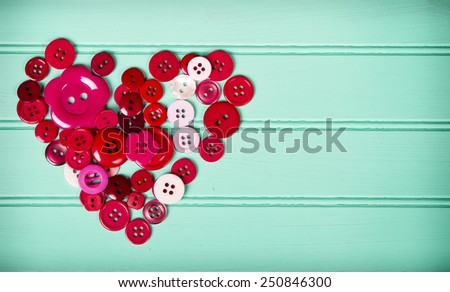 Sewing buttons in the shape of a heart on a retro turquoise background - stock photo