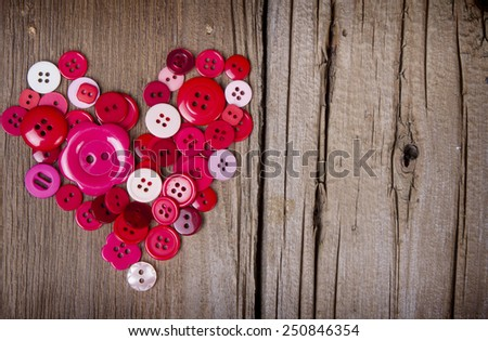 Sewing buttons in the shape of a heart on a rustic wooden background - stock photo