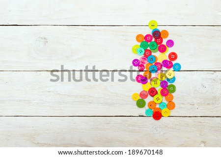 Sewing buttons on a wooden background with copy space.  - stock photo