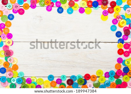 Sewing buttons on a wooden background with copy space - stock photo