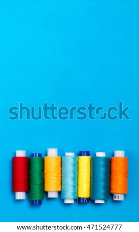 Sewing colored threads on blue fabric