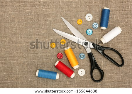 Sewing concept. Scissors, colorful  bobbin thread and buttons - stock photo