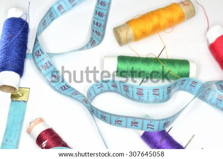 sewing fashion background ( retro blue  ruler and many colored clew  with needles for sewing )