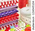 Sewing items: buttons, colorful fabrics, measuring tape, pin cushion, thimble - stock photo