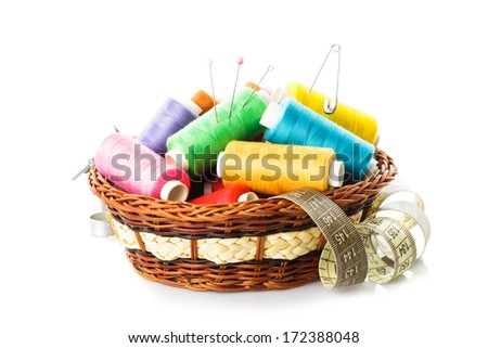 Sewing items in basket: threads, pins, meter and scissors on white - stock photo