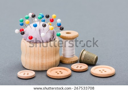 Sewing items: thread, buttons, thimble and pincushion