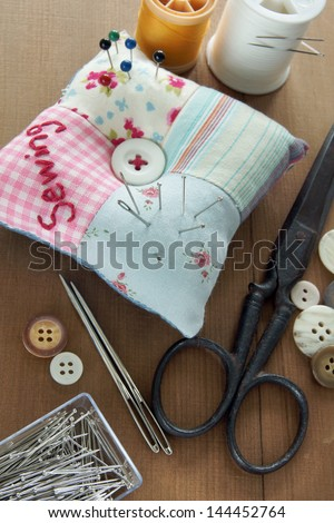 Sewing items with a vintage feel, thread, antique scissors, pins and buttons - stock photo