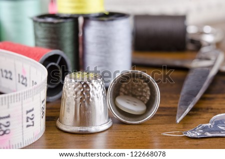 sewing kit on wood background