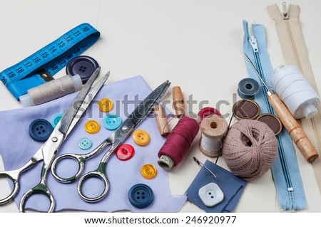 Sewing kit with scissors, spools of thread and needles on white wooden background.