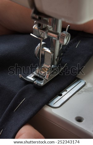 sewing machine and item of clothing - stock photo