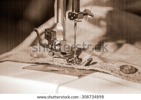 sewing machine and item of clothing. Old style, sepia - stock photo