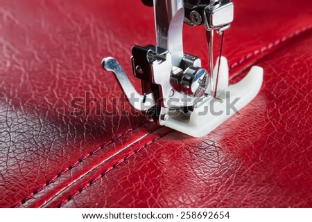 sewing machine and red leather with a seam close-up - stock photo