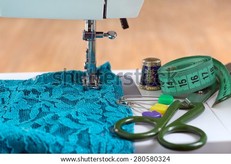 Sewing machine and sewing accessories on wooden table, selective focus - stock photo