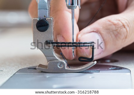 Sewing machine and thread rolling. Man hand work needles thread  - stock photo