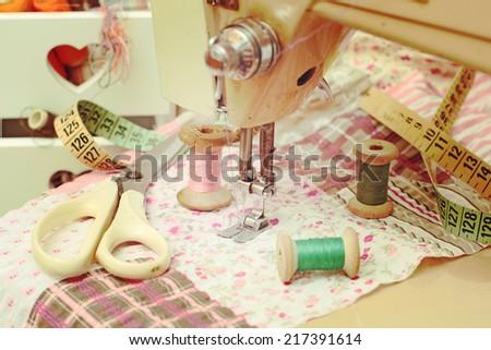 sewing machine, dressmaker scissors and thread-style retro - stock photo