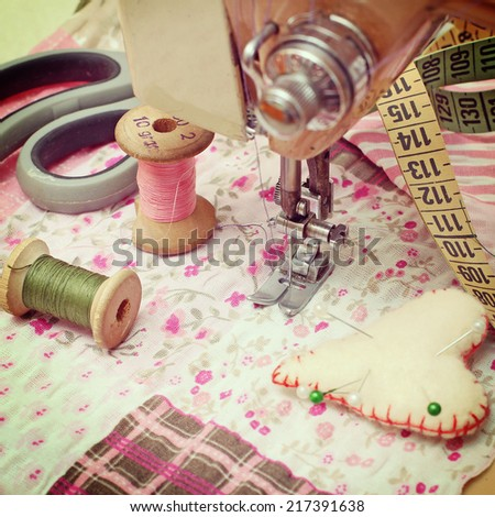 sewing machine, dressmaker scissors and thread-style retro - stock photo
