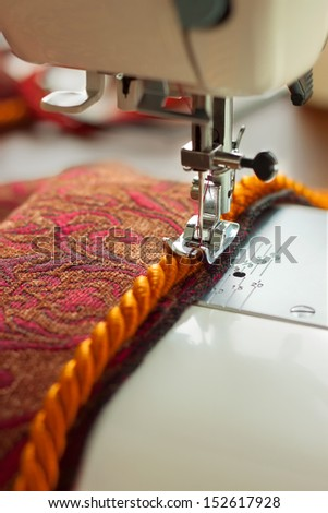 sewing machine needle and decorative edging cord - stock photo