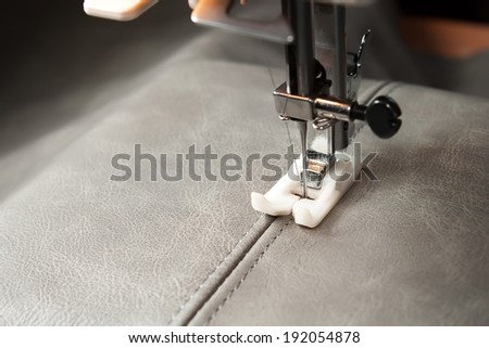 sewing machine needle and gray  leather with seam - stock photo