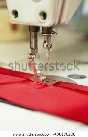 Sewing machine needle fastening satin ribbon to red piece of cloth - stock photo