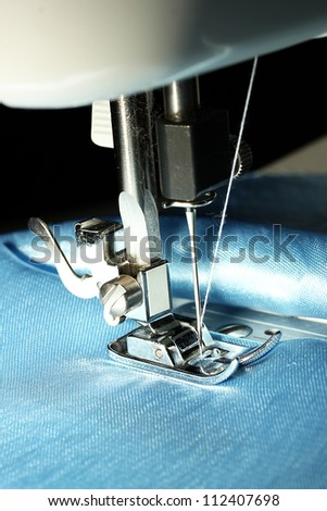 Sewing machine with blue cloth closeup - stock photo