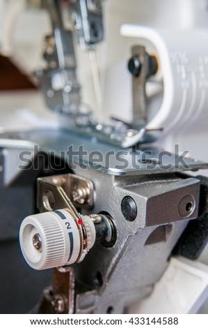 Sewing machine with fabric industrial overlock machine mechanism - stock photo