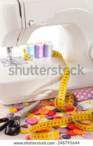 Sewing machine with many sewing utensils on a wooden box - stock photo