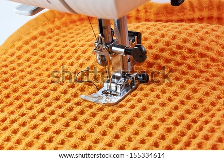 sewing machine working part with orange cloth - stock photo