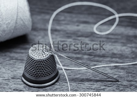 sewing needle and thimble  - stock photo