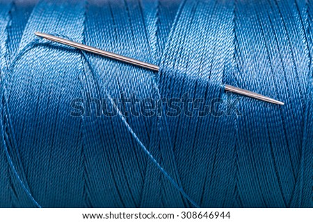 sewing needle in blue thread bobbin close up - stock photo