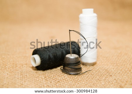 Sewing Needle, thimble and thread spool on the old cloth - stock photo