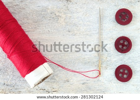 Sewing needle threaded with a red thread ready for sewing. Next , three buttons. Scene on a white wooden table . Top view. - stock photo