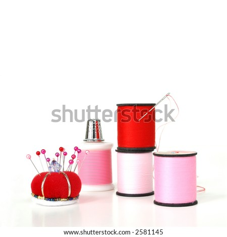 Sewing Notions on White - pink and red thread, a thimble, a threaded needle and pin cushion on a reflective white background. - stock photo