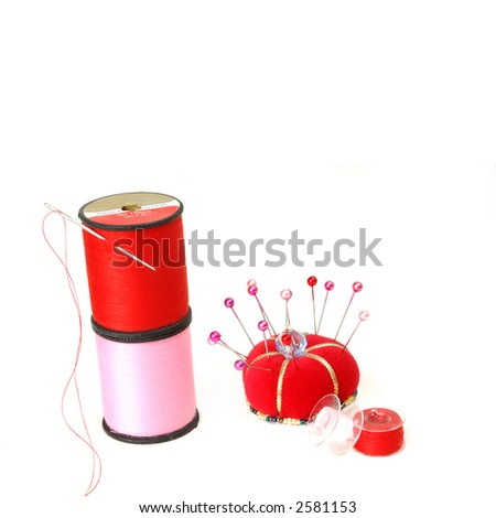Sewing Notions on White - pink and red thread, sewing machine bobbins and pin cushion on a white background. - stock photo