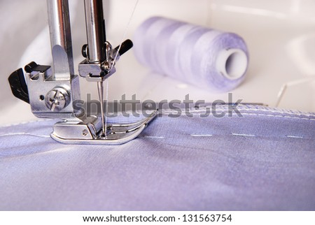 sewing process of blue cloth on the machine and two bobbins background - stock photo