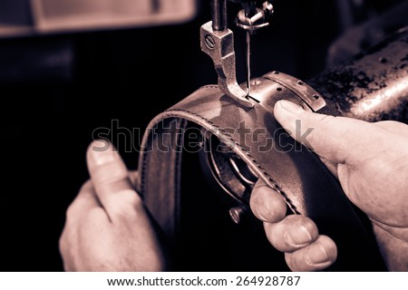 Sewing process of the leather belt. Man's hands behind sewing. Monochrome cream tone. Black and white photography.