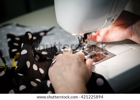Sewing Process - Women's hands behind her sew machine