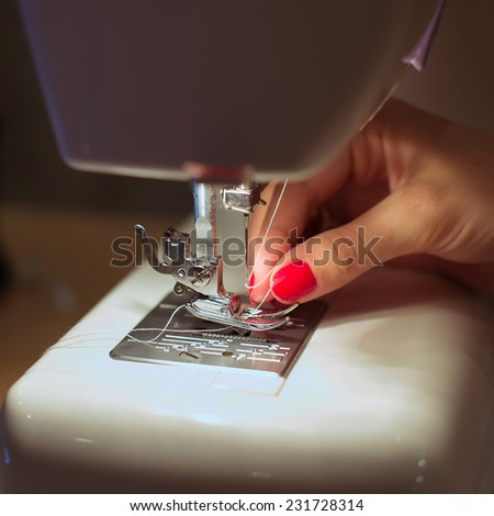Sewing Process - Women's hands behind her sewing - stock photo