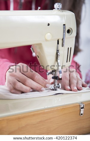 Sewing Process - Women's hands behind her sewing machine
