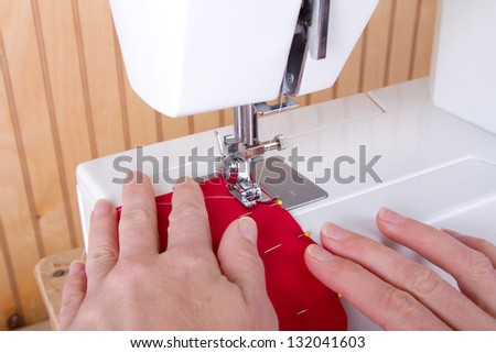 Sewing red fabric on sewing machine