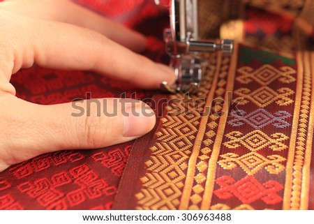 Sewing red thai cloth by sewing machine - stock photo