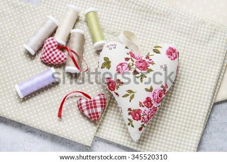 Sewing set: fabrics, threads and handmade hearts - stock photo