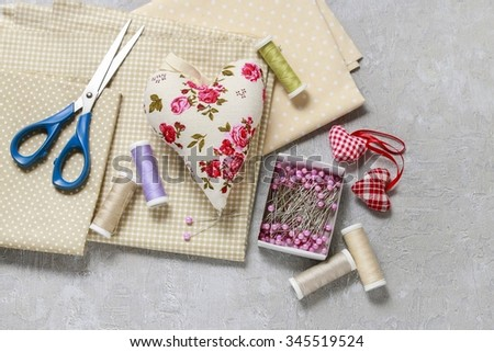 Sewing set: fabrics, threads and pins on pink background - stock photo