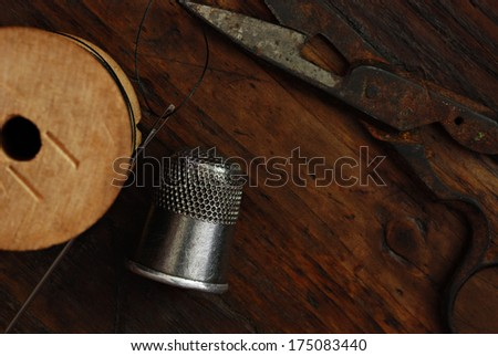 Sewing still life of antique thimble and scissors with threaded needle and wooden spool on rustic, dark wood background.  Low key natural lighting for effect.  - stock photo
