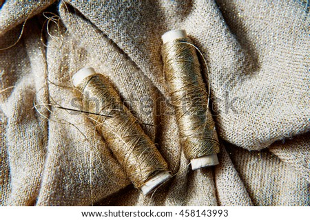 Sewing textile or cloth. Reel of thread, and golden fabric.