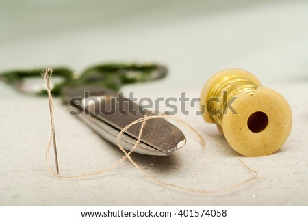 Sewing textile or cloth. Work table of a tailor. Textile tools. Scissors reel of thread, measuring tapes and natural fabric..  - stock photo